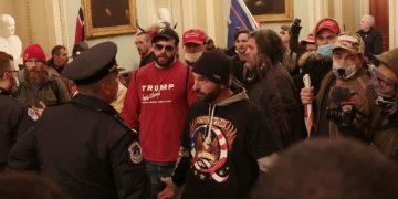 Un seguidor de QAnon, al centro, se enfrenta a un oficial el 6 de enero en el Capitolio de Washington DC. Foto: Manuel Balce/AP.