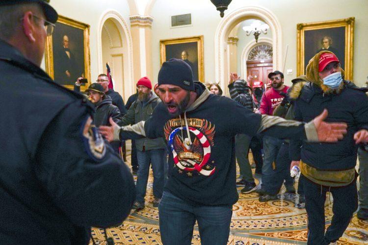 Simpatizantes del presidente saliente Donald Trump se enfrentan a la policía del Capitolio en el vestíbulo del recinto del Senado, el miércoles 6 de enero de 2021, en Washington. Foto: Manuel Balce Ceneta/AP.