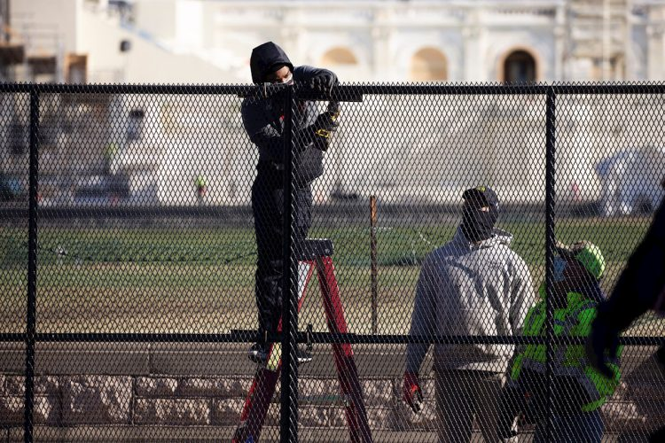 Trabajadores refuerzan la seguridad alrededor del Capitolio, al día siguiente del asalto por parte de seguidores de Donald Trump. Foto: Michael Reynolds / EFE.