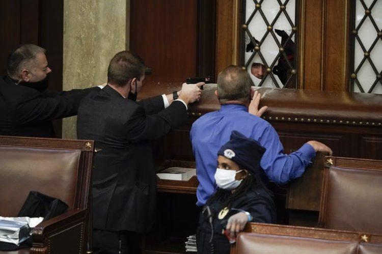Policías apuntan con sus armas a un manifestante que intenta entrar en la Cámara de Representantes del Capitolio de los EE.UU. Foto: J. Scott Applewhite/AP