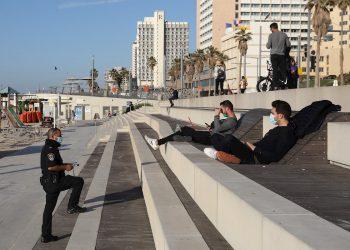 Policías interroga a personas en la playa durante un cierre nacional en Tel Aviv. Foto: ABIR SULTAN/EFE/EPA/