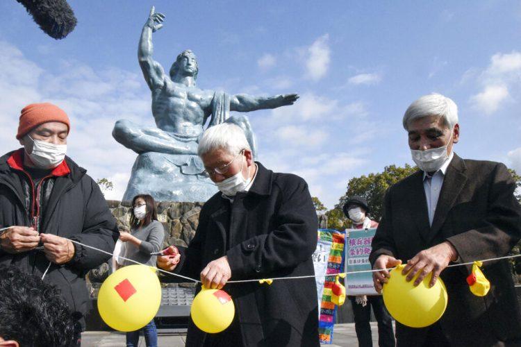 Asistentes a un acto en el Parque de la Paz, de Nagasaki, desinflan globos que simboliza la esperanza de neutralizar y destruir la ojivas nucleares. Foto: Kyodo News vía AP.
