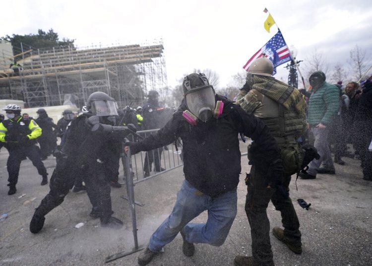 Seguidores del presidente de Estados Unidos, Donald Trump, tratan de desmontar una barrera policial, el 6 de enero de 2021, en el Capitolio, en Washington.  Foto: Julio Cortez/AP.
