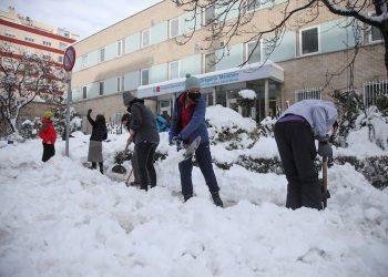 Varios voluntarios despejan con palas el acceso a una de las entradas del Hospital Gregorio Marañón de Madrid, cubierto de una gruesa capa de nieve tras el paso de la borrasca Filomena. Foto: David Fernández/EFE