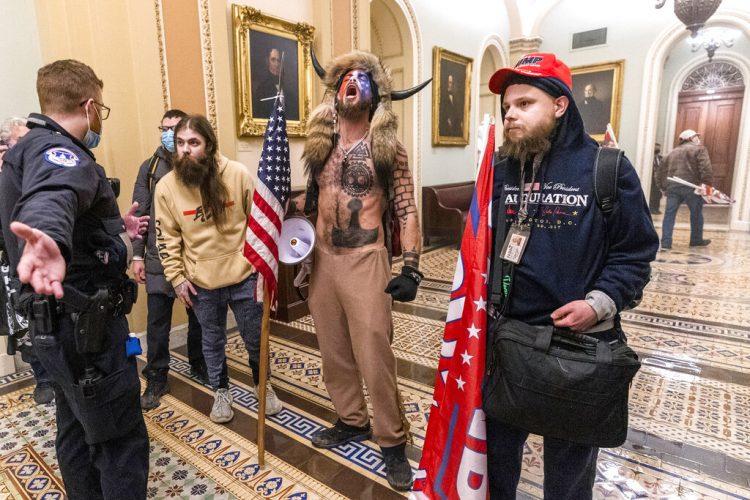 Partidarios de Donald Trump, incluido Jacob Chansley (con el torso descubierto y un sombrero de piel con cuernos), fotografiados durante la toma del Congreso el 6 de enero del 2021 en Washington. Foto: Manuel Balce Ceneta/AP.