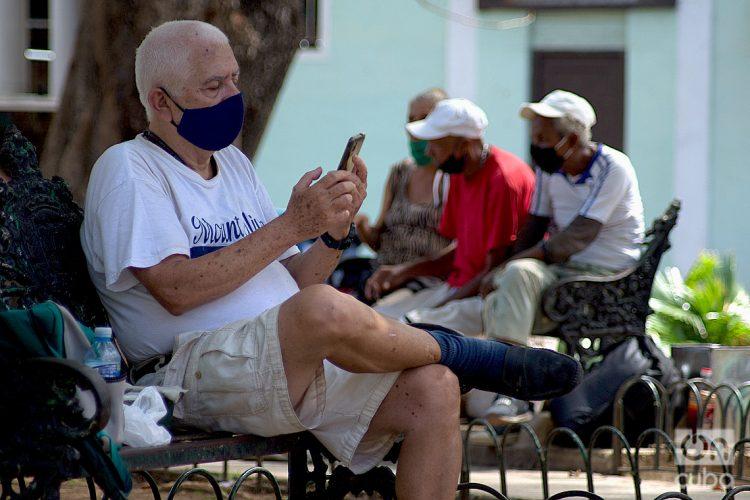 Un hombre revisa internet en su móvil en un parque de La Habana. Foto: Otmaro Rodríguez.