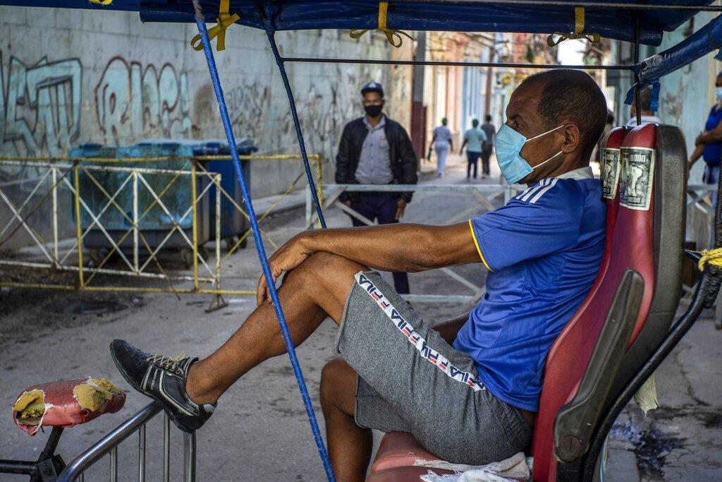 Un taxista en bicicleta espera clientes afuera de una puerta donde la policía controla el acceso a un vecindario como una forma de frenar la propagación de COVID-19 en La Habana, Cuba, el lunes 22 de febrero de 2021. Foto: AP/Ramon Espinosa.