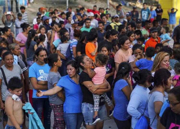Migrantes, muchos de ellos devueltos a México por la política migratoria del entonces presidente de Estados Unidos Donald Trump, esperan en final para recibir alimentos en un campamento en el puente internacional en Matamoros, México. Foto: Veronica G. Cárdenas/Ap/ archivo.