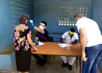 Un trabajador de la salud tomando la temperatura a una mujer en un punto de control holguinero. Foto: Trabajadores.