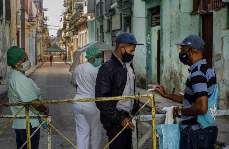 Un residente muestra su identificación a un oficial de policía que está limitando el acceso a un vecindario como una forma de frenar la propagación de la pandemia de COVID-19, mientras enfermeras están detrás en La Habana, Cuba, el lunes 22 de febrero de 2021. Foto: AP/Ramon Espinosa.