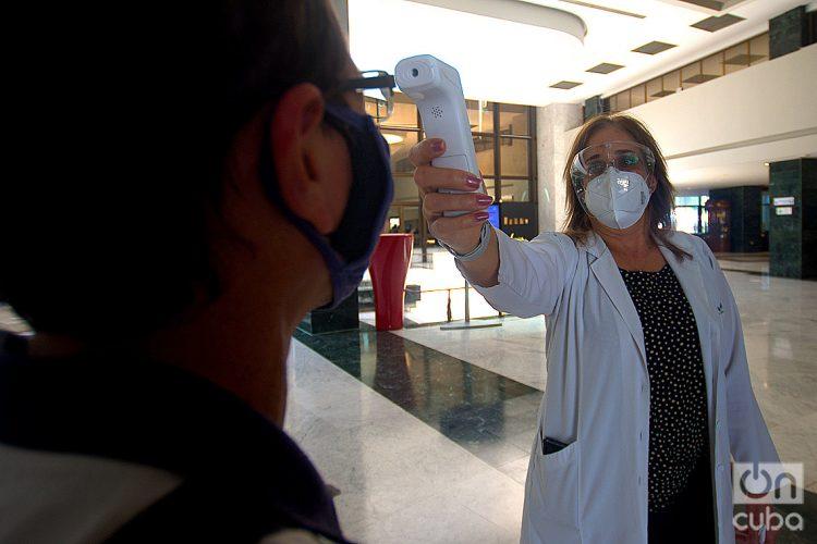 Una doctora toma la temperatura a una persona en el hotel Melià Habana, una de las instalaciones que ofrece paquetes turísticos para el aislamiento de viajeros internacionales en la capital cubana. Foto: Otmaro Rodríguez.