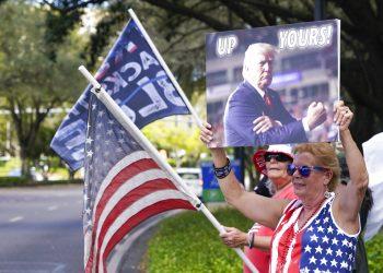Seguidores de Donald Trump ondean banderas y letreros a los conductores que pasan frente al centro de convenciones en la Conferencia de Acción Política Conservadora el sábado 27 de febrero de 2021 en Orlando, Florida. Foto: AP/John Raoux.