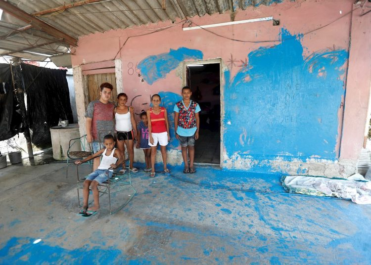 La activista disidente Anyell Valdés (3-i) posa junto a su familia en el lugar que ocupa y que fue vandalizada durante un acto de repudio, en La Habana (Cuba). Foto: Yander Zamora/Efe.
