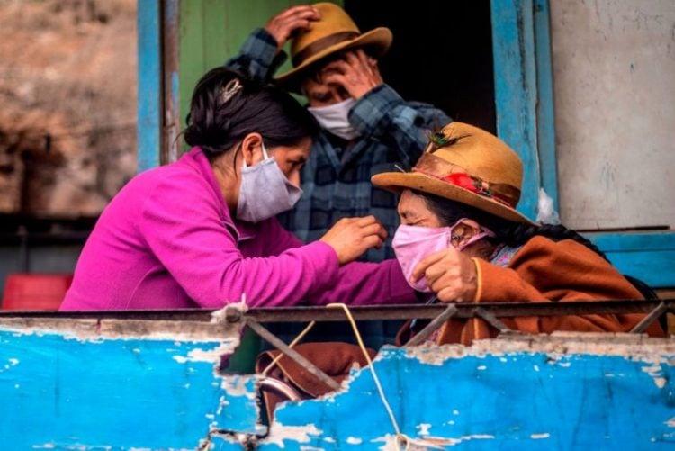Una mujer le arregla el nasobuco a su madre en una casa en Pamplona Alta, periferia sur de Lima. Foto: Ernesto Benavides/ AFP.