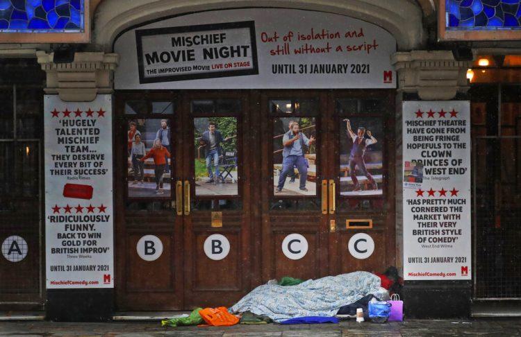 Una persona sin hogar duerme a la entrada de un teatro cerrado por la pandemia del coronavirus, en Londres, el 8 de febrero de 2021. Foto: Frank Augstein/Ap.