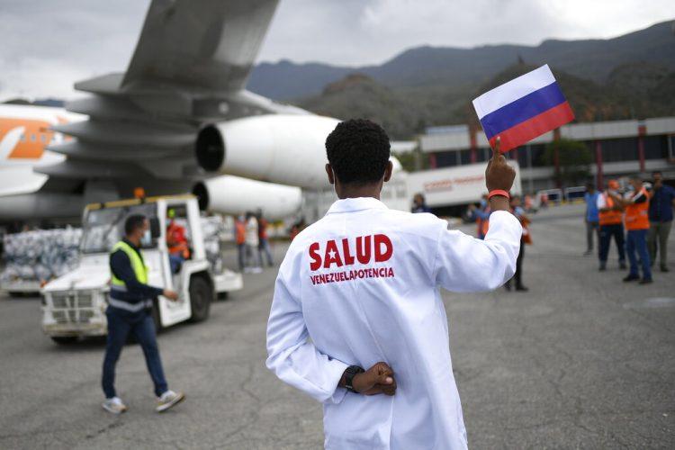 Un trabajador de la salud sostiene una bandera nacional rusa mientras es descargado un cargamento de la vacuna rusa Sputnik V contra el COVID-19, en el Aeropuerto Internacional Simón Bolívar en Maiquetía, Venezuela, el sábado 13 de febrero de 2021  Foto: Matías Delacroix/Ap.