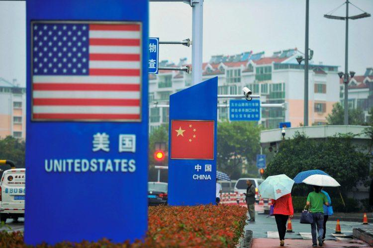 Se ven carteles con la bandera de Estados Unidos y la bandera china afuera de una tienda que vende productos extranjeros en Qingdao, en la provincia oriental de Shandong, el 19 de septiembre de 2018. Foto: AFP/Getty Images