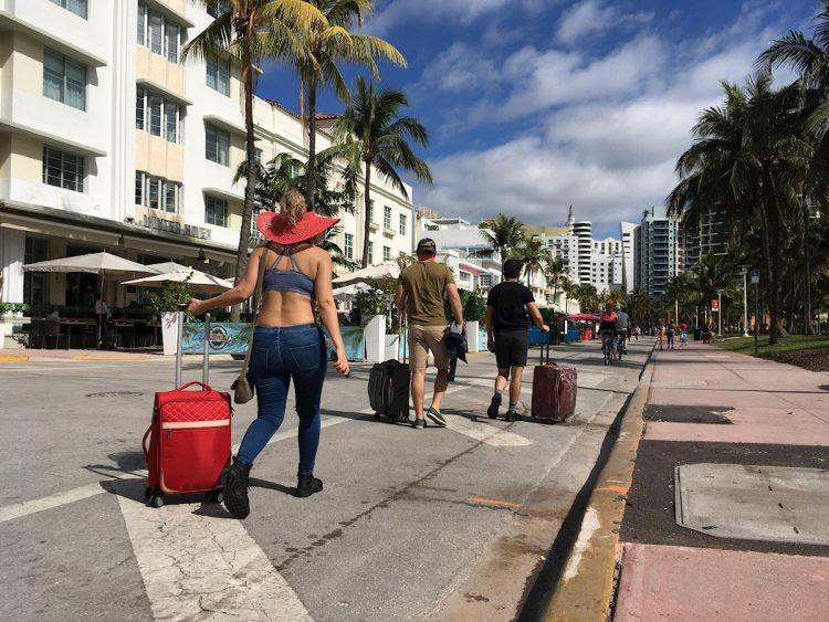 Varias personas caminan con su equipaje a través de la avenida Ocean Drive, en Miami Beach, Florida, luego de decretarse el toque de queda nocturno por sus autoridades. Foto: Ivonne Malaver / EFE.