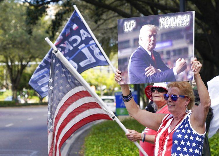 Seguidores de Donald Trump ondean banderas y letreros a los conductores que pasan frente al centro de convenciones en la Conferencia de Acción Política Conservadora el sábado 27 de febrero de 2021 en Orlando, Florida. (AP Foto/John Raoux)