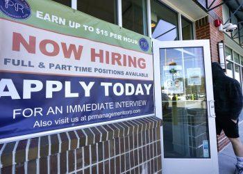 Un hombre entra a un restaurante con un cartel que anuncia contrataciones el jueves, 4 de marzo del 2021, en Salem, Nueva Hampshire. Las empresas estadounidenses añadieron 379 000 empleos en febrero, la mayor cifra desde octubre. Foto: Elise Amendola/AP.