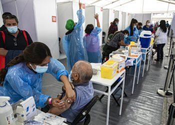 Un trabajador de la salud inocula a un anciano con una dosis de la vacuna Sinovac COVID-19 en un centro de inmunización instalado en el Estadio Bicentenario en Santiago de Chile. Foto: Esteban Félix/Ap/ archivo.