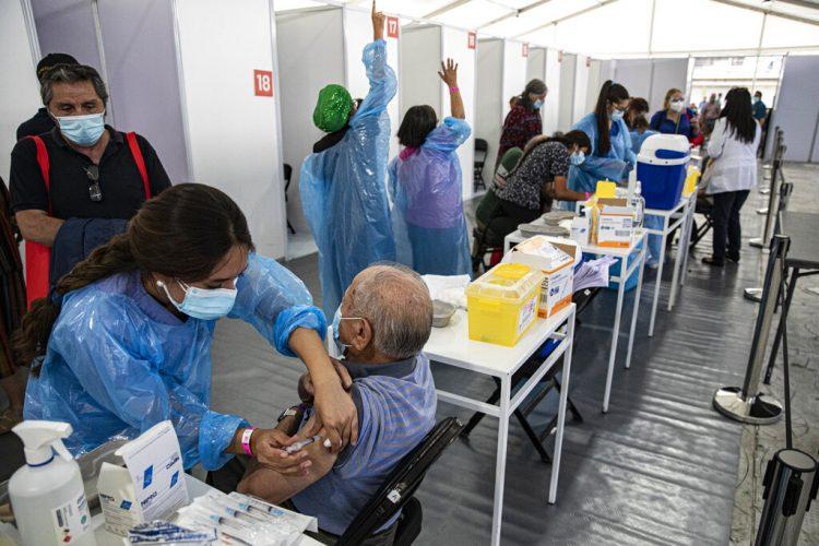 Un trabajador de la salud inocula a un anciano con una dosis de la vacuna Sinovac COVID-19 en un centro de inmunización instalado en el Estadio Bicentenario en Santiago de Chile. Foto: Esteban Félix / AP / Archivo.