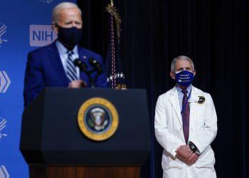 El presidente Joe Biden hace declaraciones el jueves 11 de febrero de 2021 durante una visita al Laboratorio de Patogénesis Viral, en los Institutos Nacionales de Salud, en Bethesda, Maryland. Al fondo está el doctor Anthony Fauci, director del Instituto Nacional de Alergias y Enfermedades Infecciosas. (AP Foto/Evan Vucci)