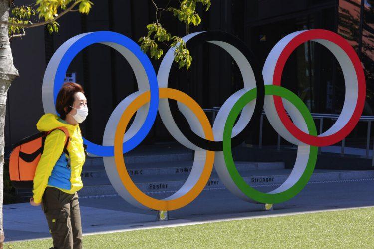 Una mujer camina frente a los anillos olímpicos en Tokio, el miércoles 10 de marzo de 2021. Foto: AP/Koji Sasahara.