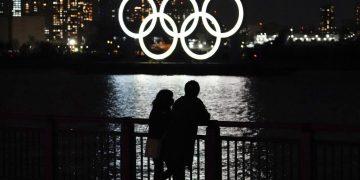 Una pareja frente al despliegue de los anillos olímpicos en el distrito de Odaiba en Tokio, el miércoles 3 de marzo de 2021. Foto: AP/Eugene Hoshiko.