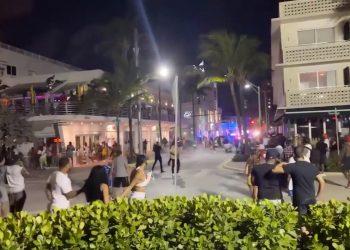 Decenas de jóvenes se enfrentan a la policía en la intersección de Ocean Drive y la calle 8, en Miami Beach. | Cortesía Miami Herald.