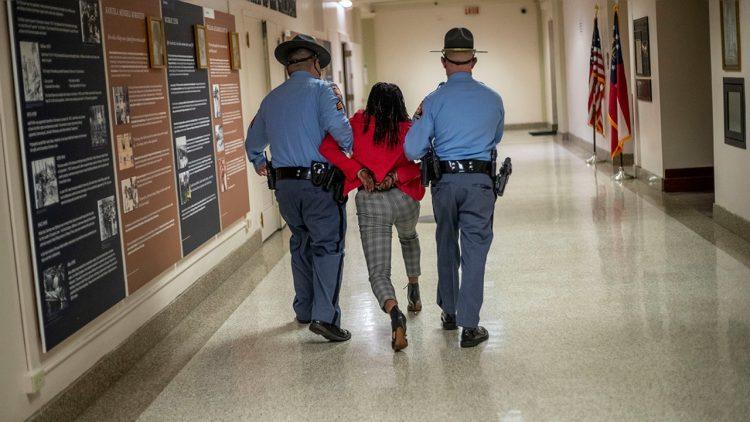 La congresista estatal demócrata Park Cannon es arrastrada por la policía fuera del Capitolio de Georgia, en Atlanta, tras protestar por la aprobación de la ley electoral de ese estado, este jueves 25 de marzo de 2021. Foto: AP.