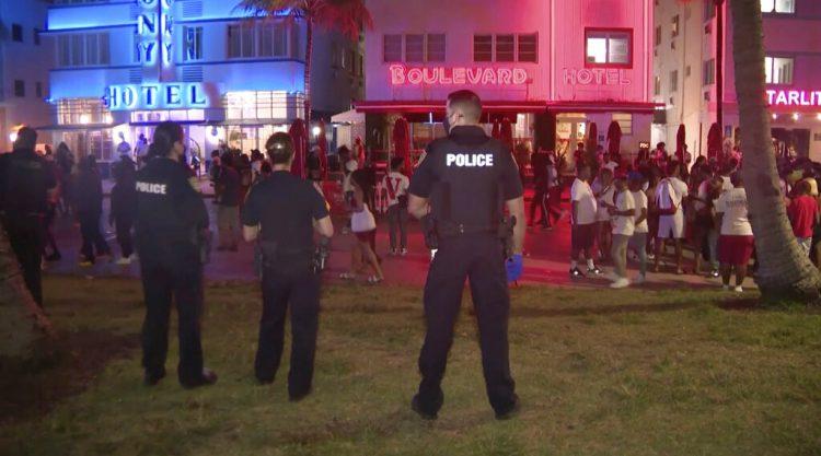 En esta imagen tomada de un video se ve a unos policías vigilando el sábado 20 de marzo de 2021 mientras una muchedumbre recorre una calle de South Beach, Miami. Foto: WPLG vía AP.