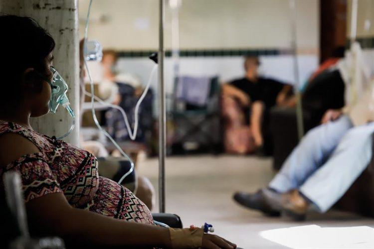 Una paciente con COVID-19 permanece sentada con una máscara de oxígeno en el Hospital de Clínicas, en San Lorenzo, Paraguay. Foto: Nathalia Aguilar / EFE.