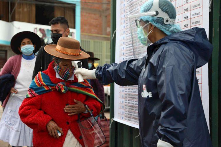 Un funcionario electoral mide la temperatura a una mujer antes de ingresar a su local de votación, en el Cusco, Perú, el domingo 11 de abril de 2021. Foto: Stringer / EFE.