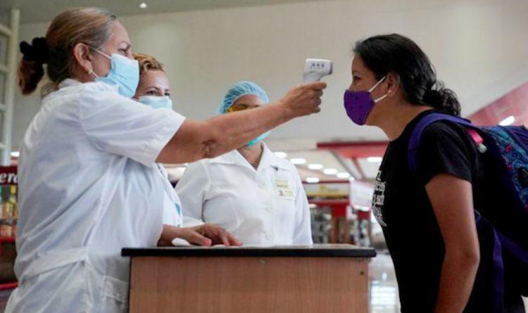 Personal sanitario cubano toma la temperatura a una viajera a su arribo a un aeropuerto de la Isla. Foto: minsap.cu