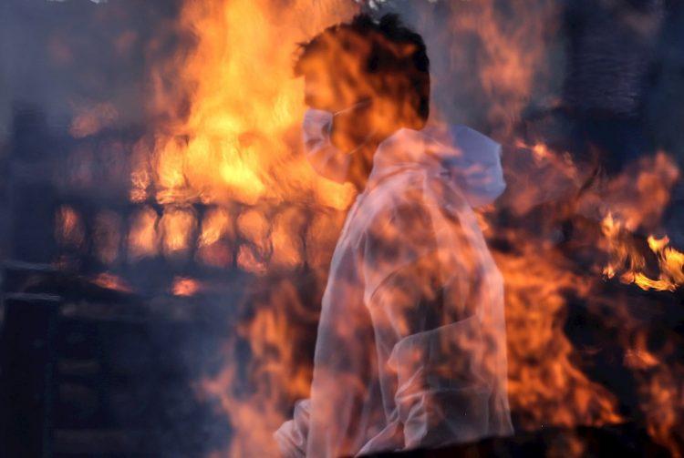 Un trabajador municipal con EPI visto tras las llamas de una de las hogueras prendidas en un crematorio para víctimas de la covid-19, este viernes en Bombay, India. Foto: EFE/ Divyakant Solanki.