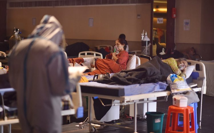 Un médico indio que usa equipo de protección personal examina a los pacientes dentro de un centro de atención a enfermos con la COVID 19 y una sala de aislamiento cerca de un hospital en Nueva Delhi, la India, el 27 de abril de 2021. Foto: Idrees Mohammed / EFE.