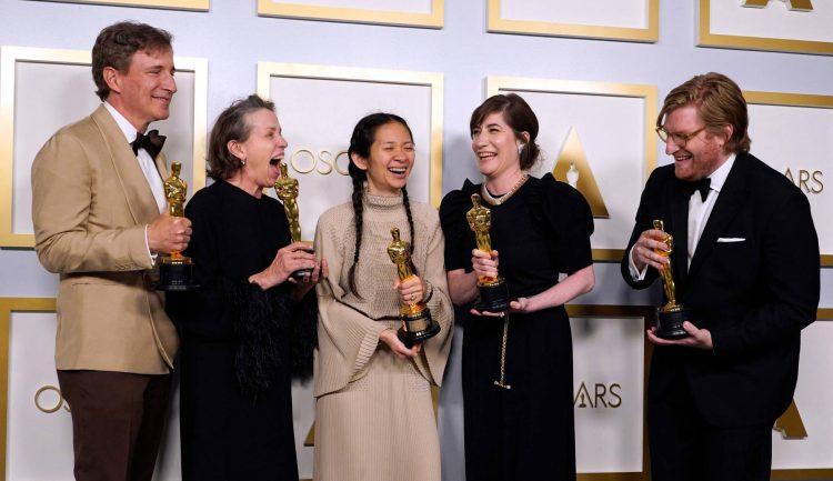 """En la noche de premiaciones, el equipo de """"Nomadland"""": Chloé Zhao y Frances McDormand (tercera y cuarta desde la derecha). Foto: AFP, vía El País."""