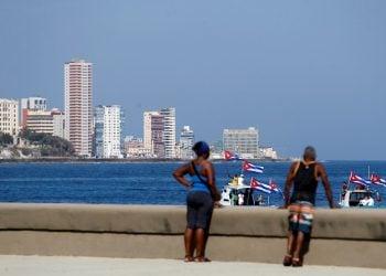Personas observan las embarcaciones que participa en la regata contra el bloqueo, en el malecón de La Habana. Foto: Yander Zamora/Efe.