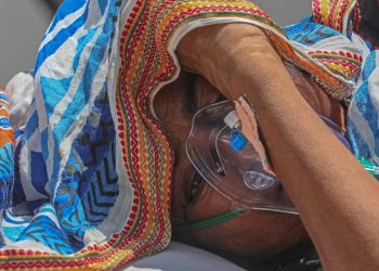Una paciente aislada por un posible caso positivo de COVID-19 recibe oxigenoterapia en un hospital de Ahmedabad, en la India. Foto: Divyakant Solanki / EFE.