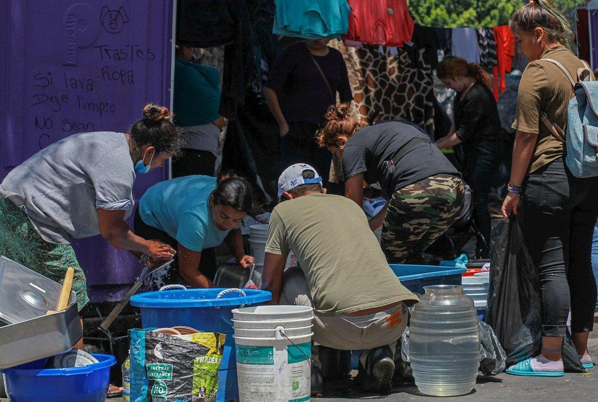 Migrantes lavan utensilios el 4 de mayo de 2021 en la plaza cívica de la Garita el Chaparral, en Tijuana, estado de Baja California (México). Foto: EFE/ Joebeth Terriquez.