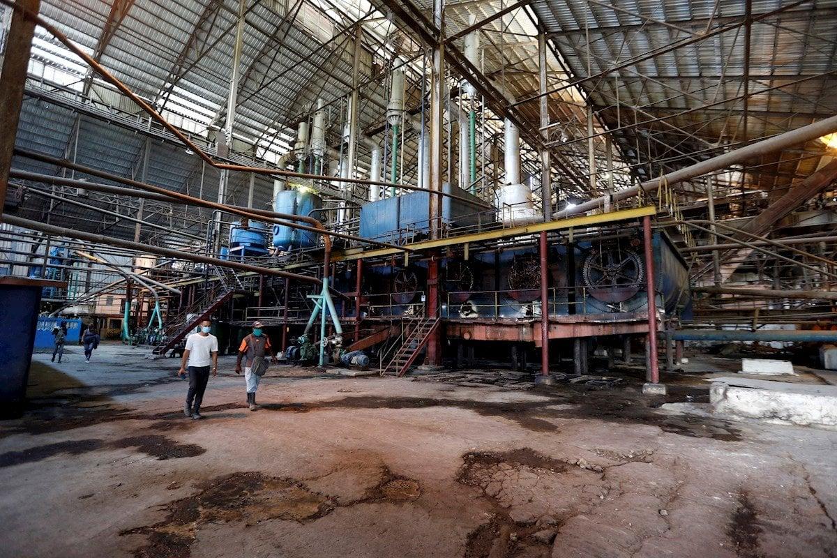 Trabajadores caminan en el Central Azucarero Boris Luis Santa Coloma, que permanece en paro de su producción de azúcar, el 29 de abril de 2021 en Madruga, Mayabeque (Cuba). Foto: EFE/Ernesto Mastrascusa.