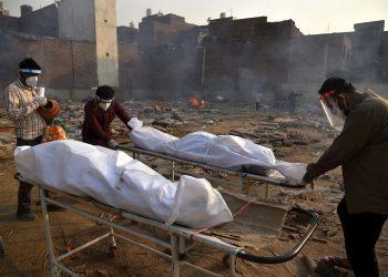 Un cuerpo es preparado para los últimos ritos en piras funerarias para las víctimas de COVID-19, en un campo de cremación improvisado en Nueva Delhi, la India, el 1 de mayo de 2021. Foto: Idrees Mohammed / EFE.
