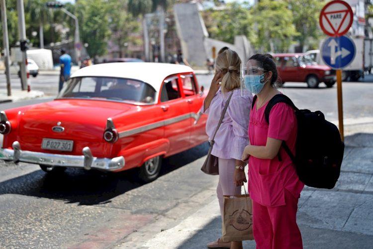 Dos mujeres esperan un taxi en una calle de La Habana. Foto: Yander Zamora/EFE.