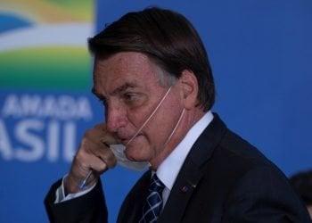 El presidente de Brasil, Jair Bolsonaro, se quita una mascarilla en un acto en el Palacio do Planalto, en la ciudad de Brasilia. Foto: Joédson Alves / EFE.