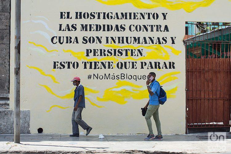 Dos hombres pasan frente a un cartel contra el embargo de EE.UU. a Cuba, en La Habana. Foto: Otmaro Rodríguez.