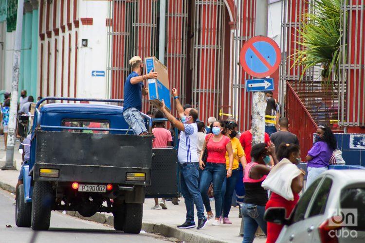 Personas cargan mercancías compradas en Moneda Libremente Convertible, en el centro comercial Carlos III, en La Habana. Foto: Otmaro Rodríguez.