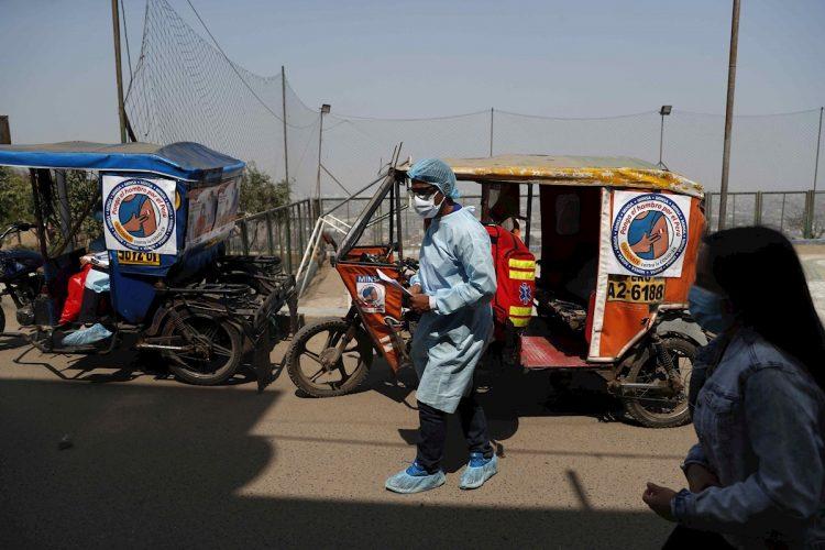 Mototaxis transportan personal de la salud para la vacunación anticovid, en el Cerro El Agustino, en Lima, Perú. Foto: Paolo Aguilar / EFE.