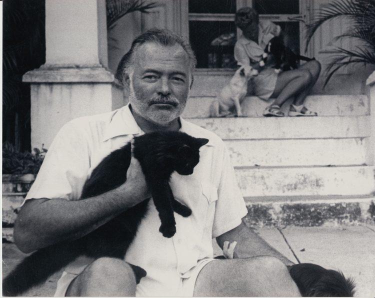 Hemingway y Mary en el portal de su casa habanera con los gatos. | Archivo PBS