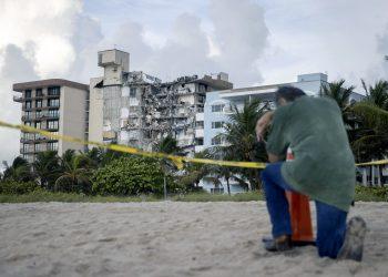 Un hombre ora en la plaza frente al edificio que se derrumbó la semana pasada en Surfside, Florida. Foto: Joe Readly / Getty.